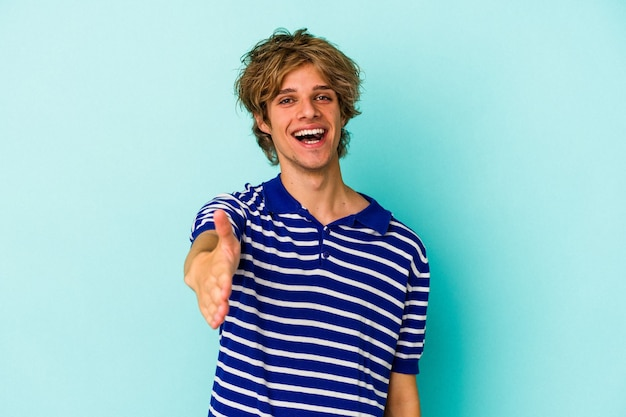 Young caucasian man with make up isolated on blue background  stretching hand at camera in greeting gesture.