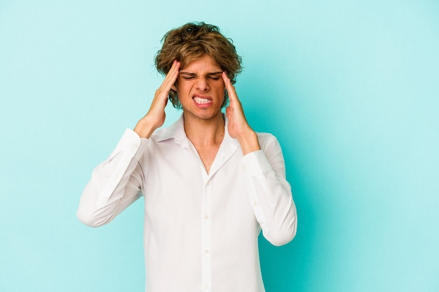Young caucasian man with make up isolated on blue background  touching temples and having headache.
