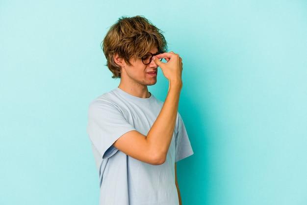 顔の正面に触れて、頭痛を持っている青い背景に孤立したメイクアップの若い白人男性。