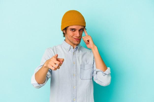 青の背景に孤立したメイクアップの若い白人男性は、指で寺院を指して、考え、タスクに焦点を当てています。