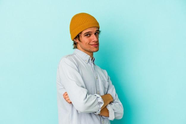 Молодой кавказский человек с макияжем, изолированные на синем фоне, подозрительный, неуверенный, исследует вас.