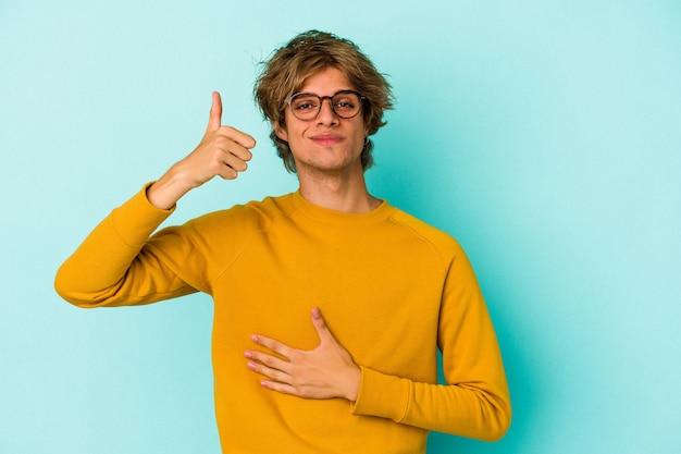 青い背景に分離されたメイクアップを持つ若い白人男性は、おなかに触れ、優しく微笑んで、食事と満足の概念。