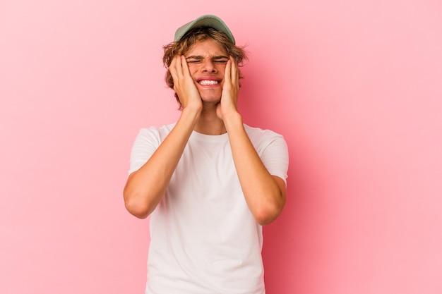 ピンクの背景に孤立したメイクアップの若い白人男性が泣いて、何かに不満、苦痛と混乱の概念。