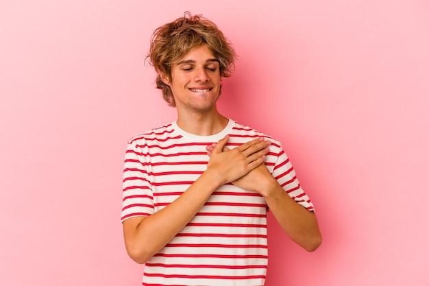 Молодой кавказский мужчина с макияжем, изолированным на розовом фоне, имеет дружелюбное выражение, прижимая ладонь к груди. концепция любви.