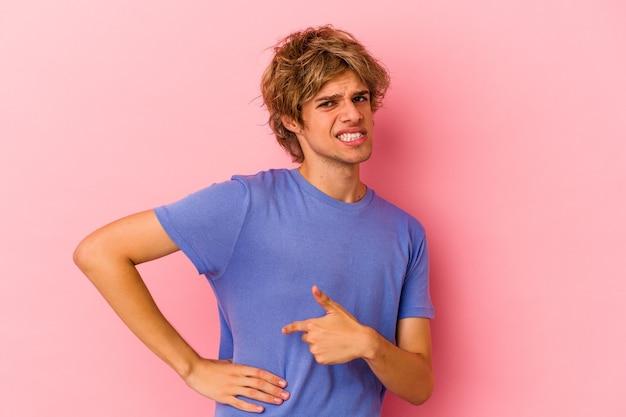 肝臓の痛み、胃の痛みを持っているピンクの背景に分離されたメイクアップの若い白人男性。