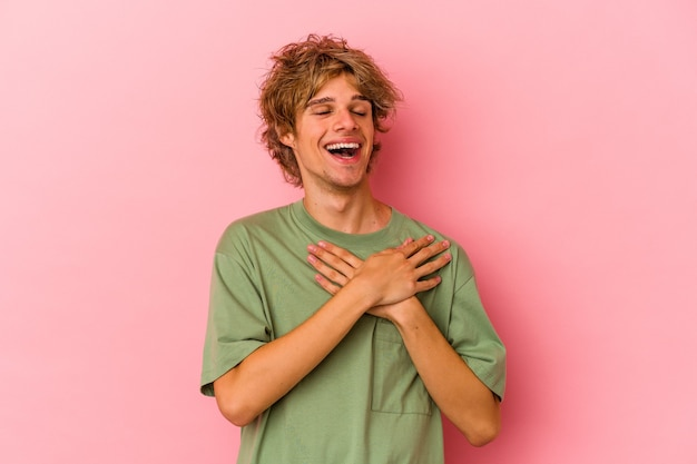 Young caucasian man with make up isolated on pink background has friendly expression, pressing palm to chest. love concept.