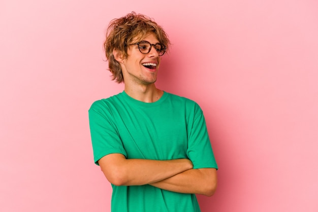 Young caucasian man with make up isolated on pink background smiling confident with crossed arms.