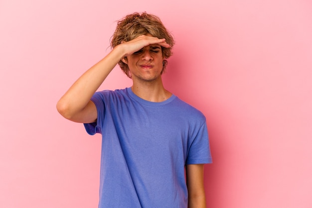 Young caucasian man with make up isolated on pink background touching temples and having headache.