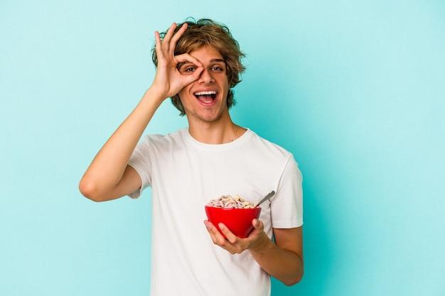 化粧をした若い白人男性は、青い背景に分離されたシリアルボウルを興奮させ、目のジェスチャーを維持します。