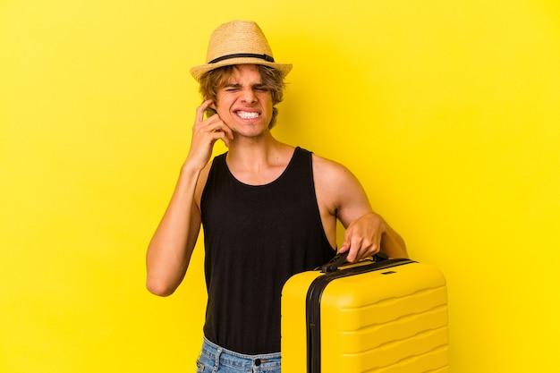 手で耳を覆う黄色の背景に孤立して旅行に行く化粧をしている若い白人男性。