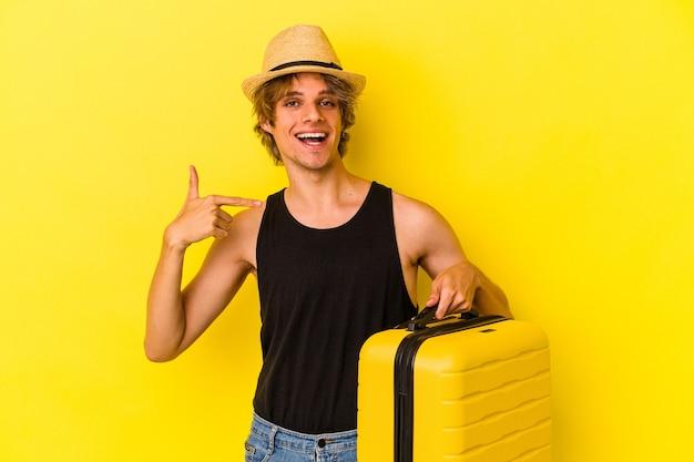 誇りと自信を持って、シャツのコピースペースを手で指している黄色の背景の人に孤立して旅行に行く化粧をしている若い白人男性
