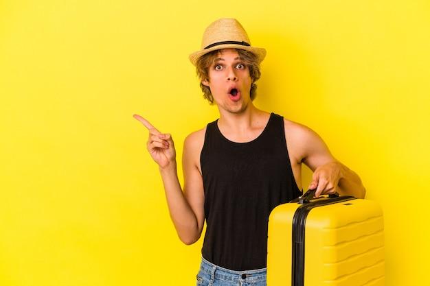 Молодой кавказский мужчина с косметикой собирается путешествовать, изолирован на желтом фоне, указывая в сторону