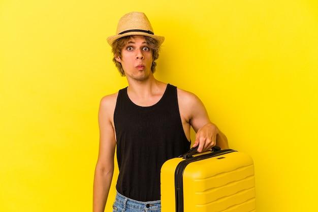 Молодой кавказский человек с косметикой собирается путешествовать, изолированные на желтом фоне, пожимает плечами и смущенно открывает глаза.