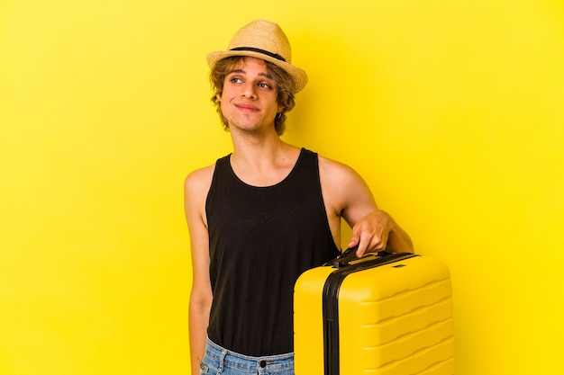Young caucasian man with makeup going to travel isolated on yellow background  dreaming of achieving goals and purposes Premium Photo