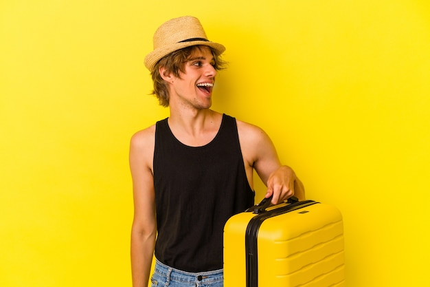 Young caucasian man with makeup going to travel isolated on yellow background  looks aside smiling, cheerful and pleasant.