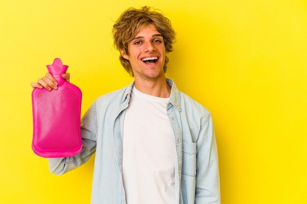 노란색 배경에 격리된 뜨거운 물 봉지를 들고 화장을 한 젊은 백인 남자는 행복하고 웃고 쾌활합니다.