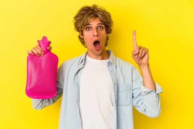 아이디어, 영감 개념을 가진 노란색 배경에 고립 된 뜨거운 물 가방을 들고 화장을 한 젊은 백인 남자.