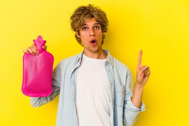 いくつかの素晴らしいアイデア、創造性の概念を持っている黄色の背景に分離された水の熱い袋を保持している化粧をしている若い白人男性。