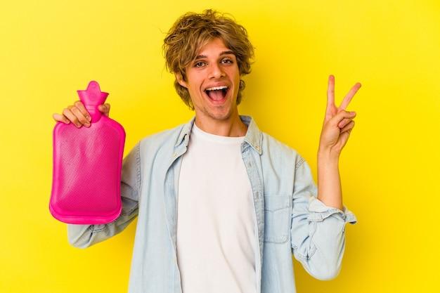 黄色の背景に分離された熱い水の袋を持って化粧をしている若い白人男性は、指で平和のシンボルを喜んで気楽に示しています。