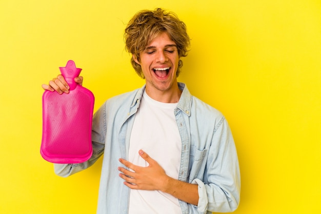 笑って楽しんで黄色の背景に分離された水の熱い袋を保持している化粧の若い白人男性。