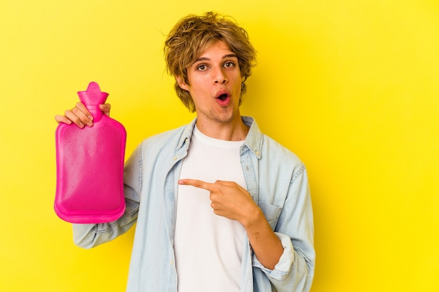 측면을 가리키는 노란색 배경에 격리된 뜨거운 물 가방을 들고 화장을 한 젊은 백인 남자