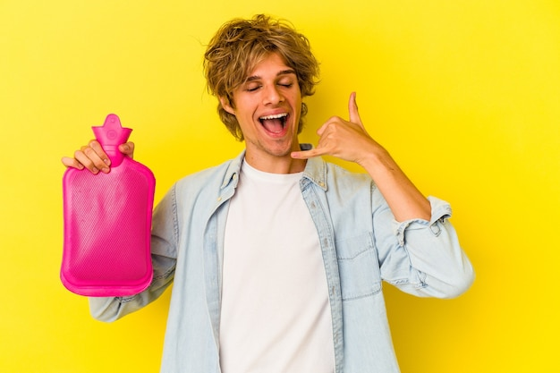 노란색 배경에 격리된 뜨거운 물 봉지를 들고 화장을 한 젊은 백인 남자가 손가락으로 휴대전화 통화 제스처를 보여줍니다.