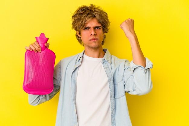카메라에 주먹을 보여주는 노란색 배경에 고립 된 뜨거운 물 가방을 들고 화장을 한 젊은 백인 남자, 공격적인 표정.