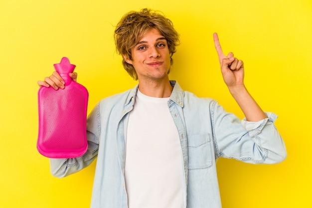 노란색 배경에 격리된 뜨거운 물 봉지를 들고 화장을 한 젊은 백인 남자가 손가락으로 1위를 보여줍니다.
