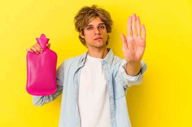 黄色の背景に分離された熱い水の袋を保持している化粧をしている若い白人男性は、一時停止の標識を示している手を伸ばして立って、あなたを防ぎます。