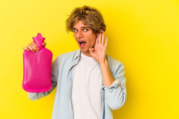 ゴシップを聴こうとしている黄色の背景に分離された水の熱い袋を保持している化粧の若い白人男性。
