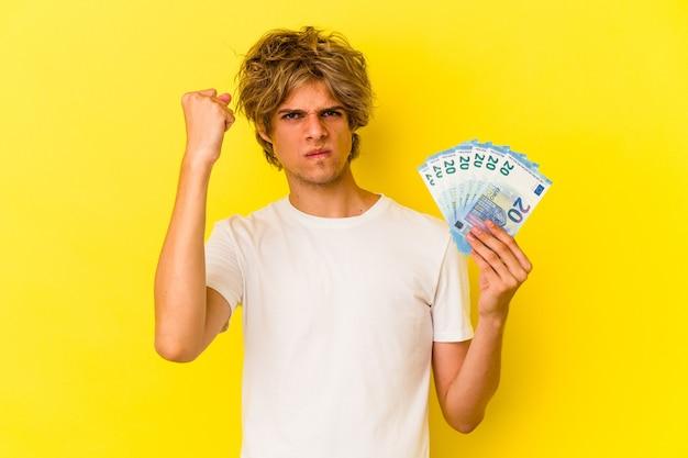 노란색 배경에 격리된 지폐를 들고 화장을 한 젊은 백인 남자는 카메라에 주먹을 대고 공격적인 표정을 짓고 있습니다.