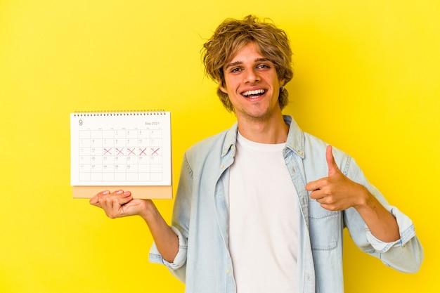 Молодой кавказский человек с макияжем, держащий календарь, изолированный на желтом фоне, улыбается и поднимает большой палец вверх