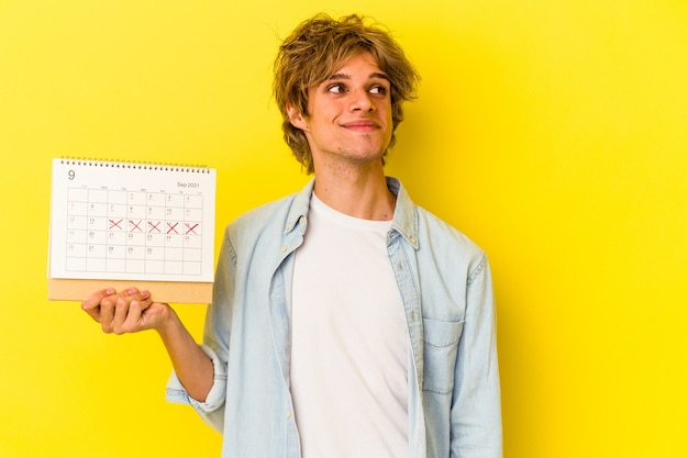 Young caucasian man with makeup holding calendar isolated on yellow background  dreaming of achieving goals and purposes Premium Photo