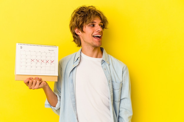 Young caucasian man with makeup holding calendar isolated on yellow background  looks aside smiling, cheerful and pleasant.