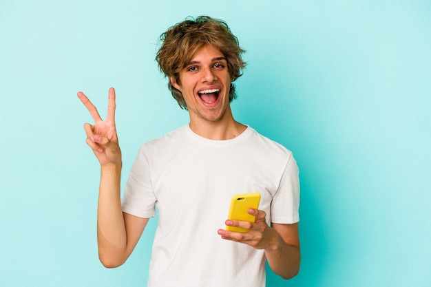 Young caucasian man with makeup holding mobile phone isolated on blue background  joyful and carefree showing a peace symbol with fingers.