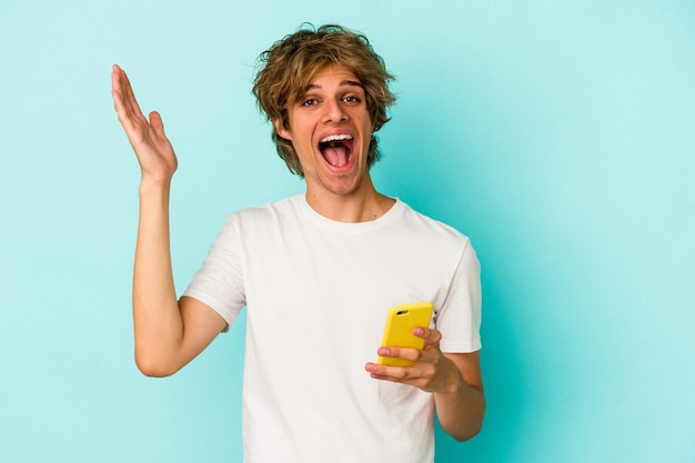 Young caucasian man with makeup holding mobile phone isolated on blue background  receiving a pleasant surprise, excited and raising hands.