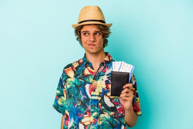 Молодой кавказский человек с косметикой, держащей паспорт, изолированный на синем фоне, смущен, чувствует себя сомнительным и неуверенным.