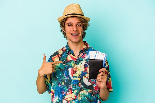Молодой кавказский мужчина с косметикой, держащий паспорт, изолированный на синем фоне, человек, указывающий рукой на пространство для копирования рубашки, гордый и уверенный