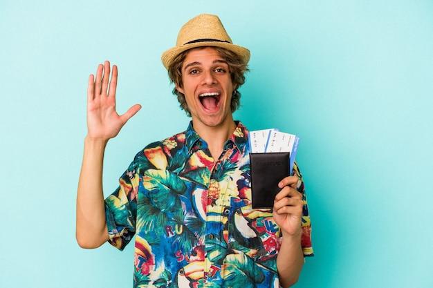 青い背景に分離されたパスポートを保持している化粧の若い白人男性は、嬉しい驚きを受け取り、興奮し、手を上げます。