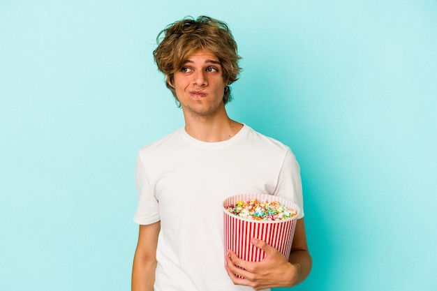 Young caucasian man with makeup holding popcorn isolated on blue background  confused, feels doubtful and unsure.