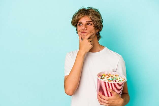 Young caucasian man with makeup holding popcorn isolated on blue background  looking sideways with doubtful and skeptical expression.
