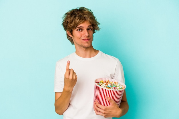 Young caucasian man with makeup holding popcorn isolated on blue background  pointing with finger at you as if inviting come closer.
