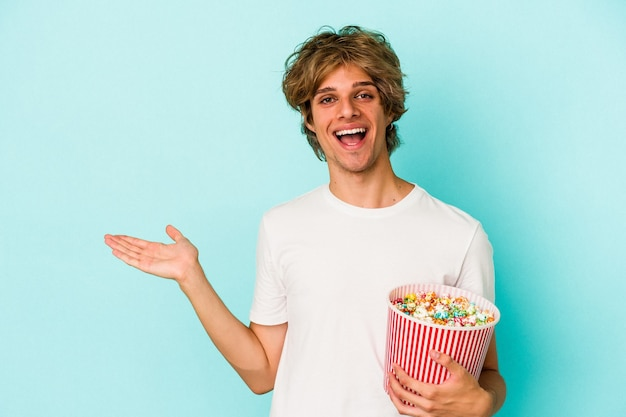 Young caucasian man with makeup holding popcorn isolated on blue background  showing a copy space on a palm and holding another hand on waist.