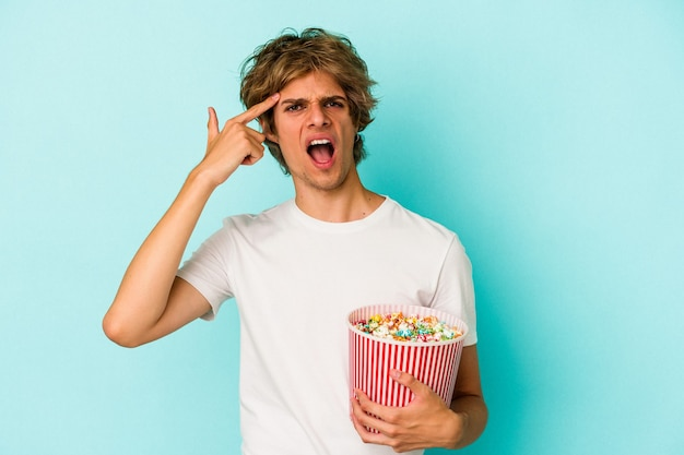 Young caucasian man with makeup holding popcorn isolated on blue background  showing a disappointment gesture with forefinger.