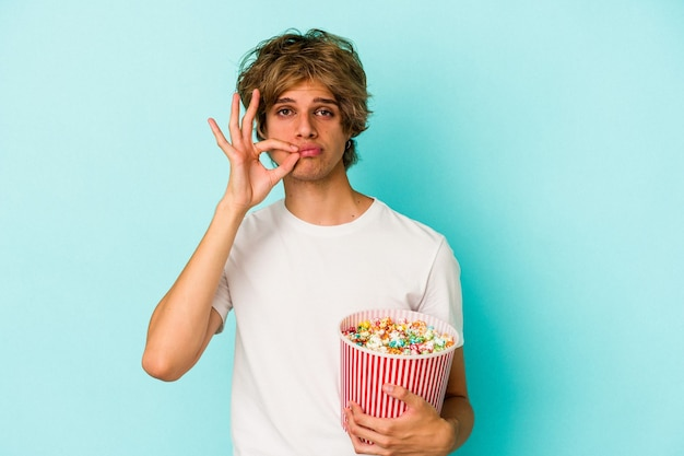 Young caucasian man with makeup holding popcorn isolated on blue background  with fingers on lips keeping a secret.