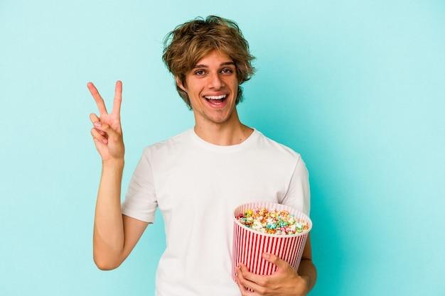 青い背景に分離されたポップコーンを持って化粧をしている若い白人男性は、指で平和のシンボルを喜んで気楽に示しています。
