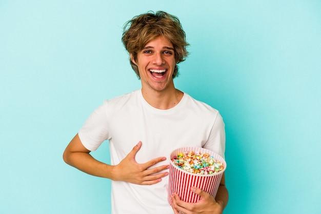 笑って楽しんで青い背景に分離されたポップコーンを保持している化粧の若い白人男性。