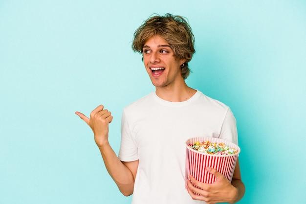 青い背景のポイントで分離されたポップコーンを持って、親指の指を離れて、笑って、のんきな化粧をしている若い白人男性。