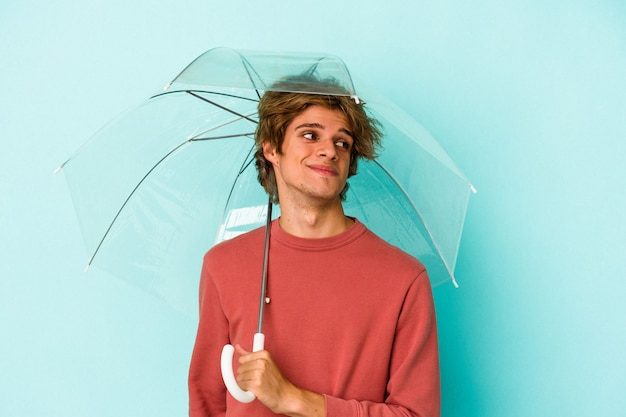 Young caucasian man with makeup holding umbrella isolated on blue background  dreaming of achieving goals and purposes