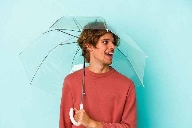 Young caucasian man with makeup holding umbrella isolated on blue background  looks aside smiling, cheerful and pleasant.